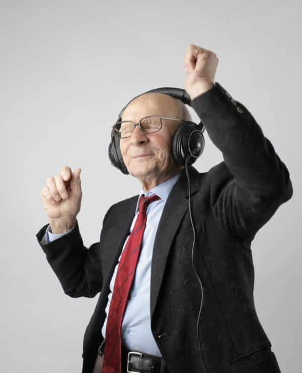 Elderly man dancing while listening to music with headphones
